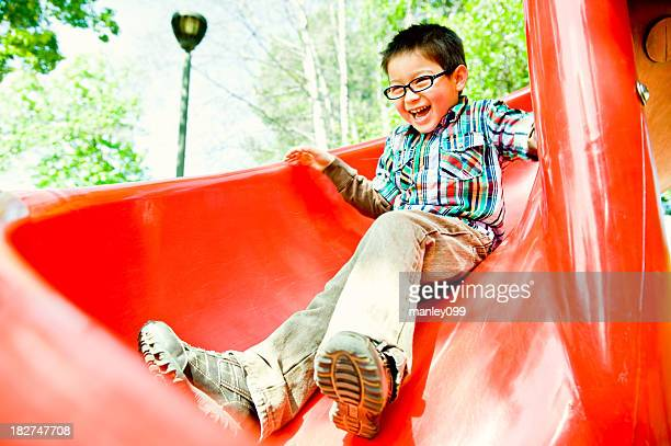 happy boy on red slide