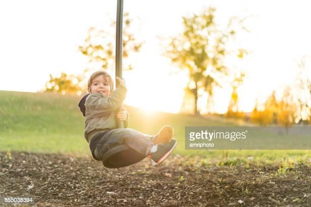 niño feliz en tirolina en día soleado de otoño - columpiarse fotografías e imágenes de stock