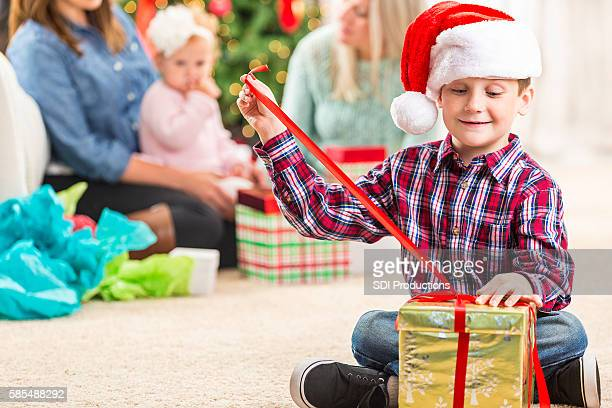 Happy boy opens gift at Christmastime