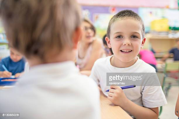 Heureux garçon peinture dans la salle de classe