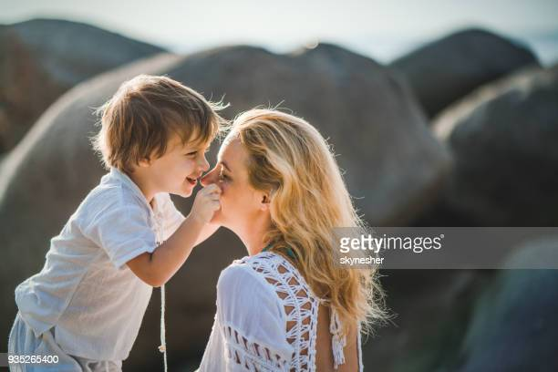 Happy boy pinching mother's cheeks during summer day.