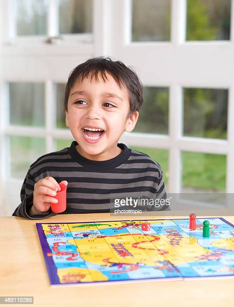 happy boy playing board game - game board stock photos and pictures