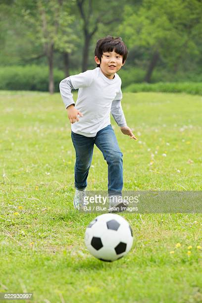 Happy boy playing football on the grass