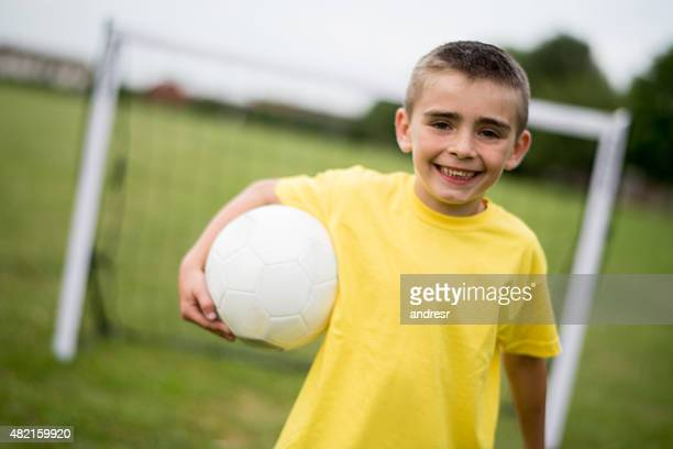happy boy playing football - one boy only stock pictures, royalty-free photos & images