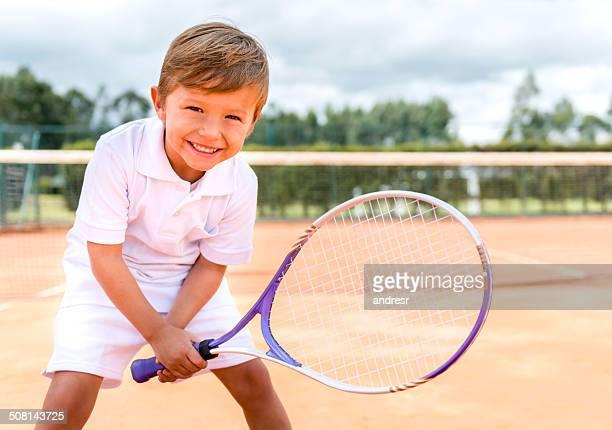 Happy boy playing tennis