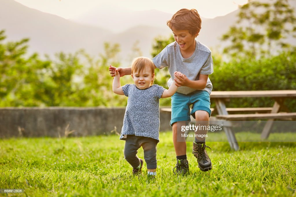 Happy boy playing with toddler on grassy field : Stock Photo