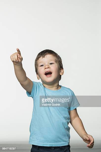 Happy boy pointing against white background