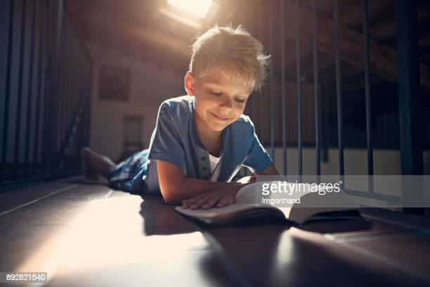 Happy boy reading a book on the floor