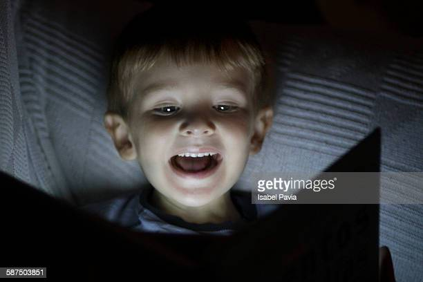 Happy boy reading in the night