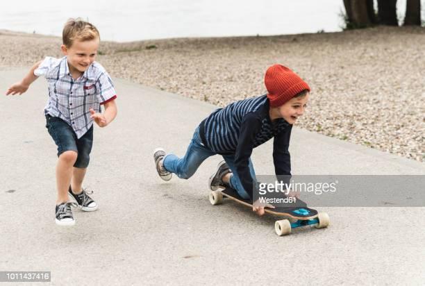 happy boy running next to brother on skateboard - 4 5 años fotografías e imágenes de stock