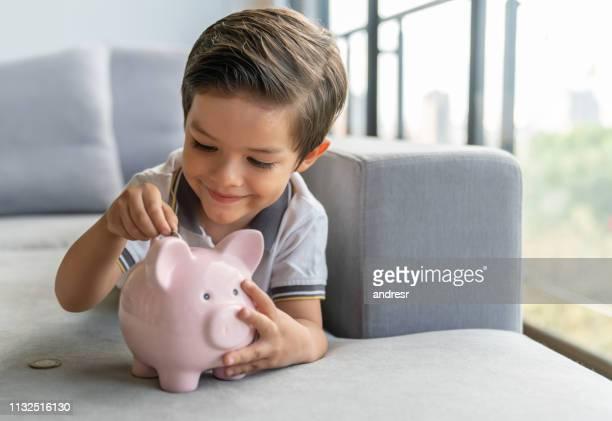 gelukkige jongen geld te besparen in zijn spaarpot - spaarvarken stockfoto's en -beelden
