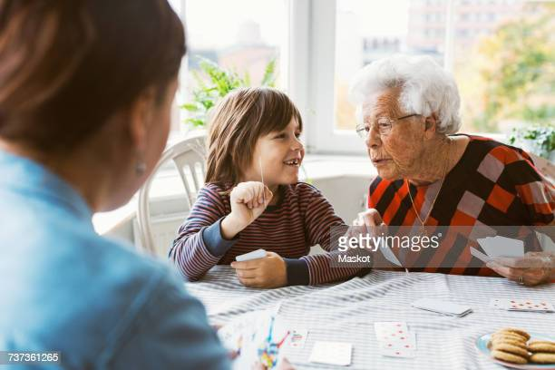 happy boy showing playing card with great grandmother at home - poker card game stock photos and pictures