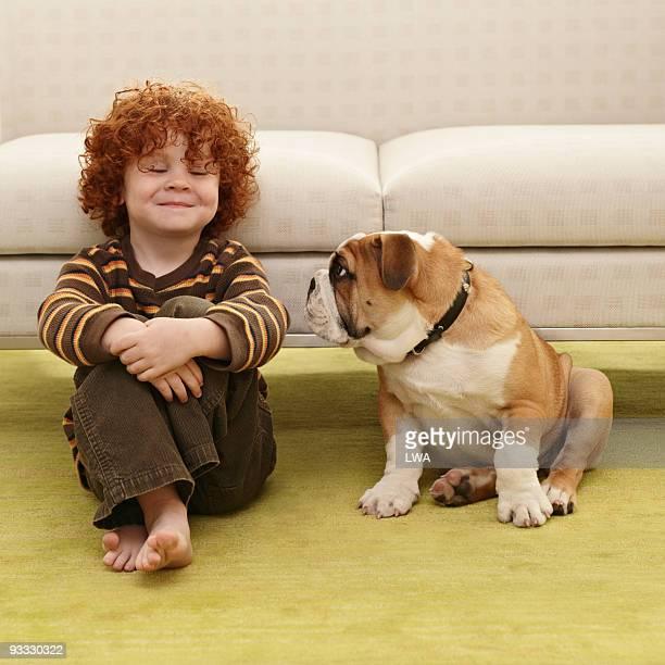Happy Boy Sitting Next To Bulldog Puppy