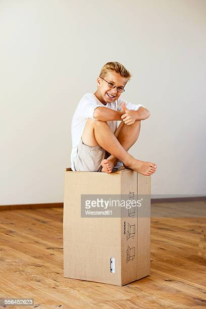 Happy boy sitting on cardboard box in an empty room showing thumb up