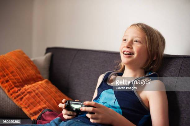 Happy boy sitting on sofa and playing video game