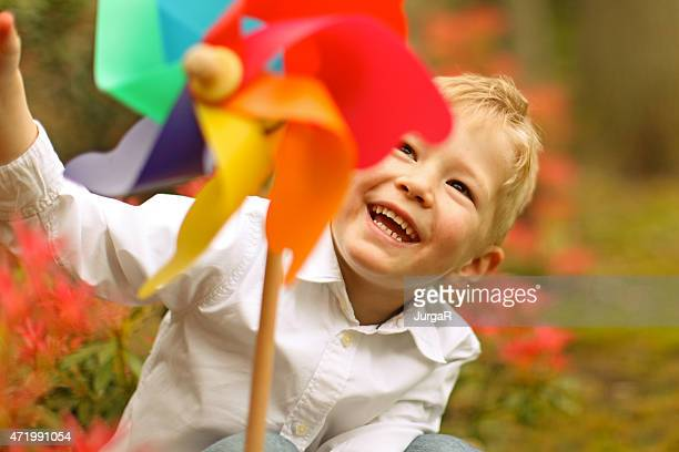 Happy Boy Spinning Pinwheel Toy in a Park