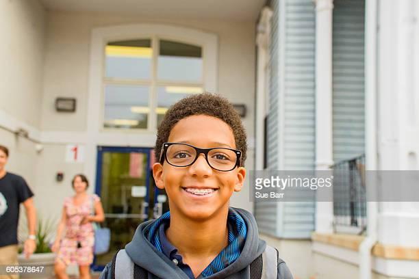 Happy boy standing in front of school