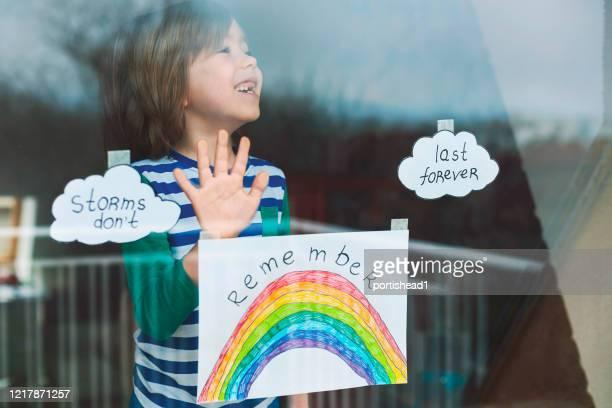 happy boy sticking his drawings on home window during the covid-19 crisis - inquadratura fissa foto e immagini stock