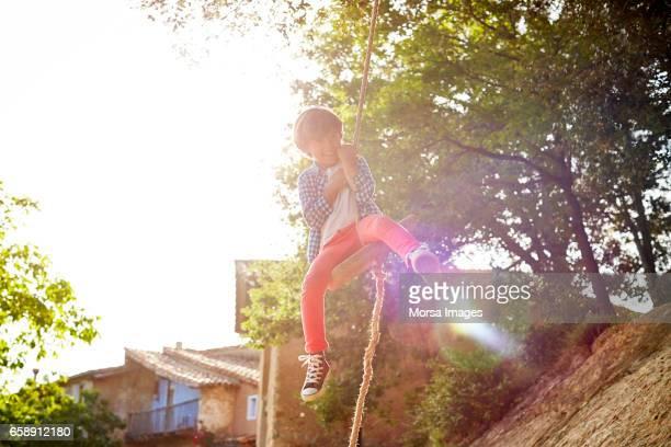 Happy boy swinging on rope swing at backyard