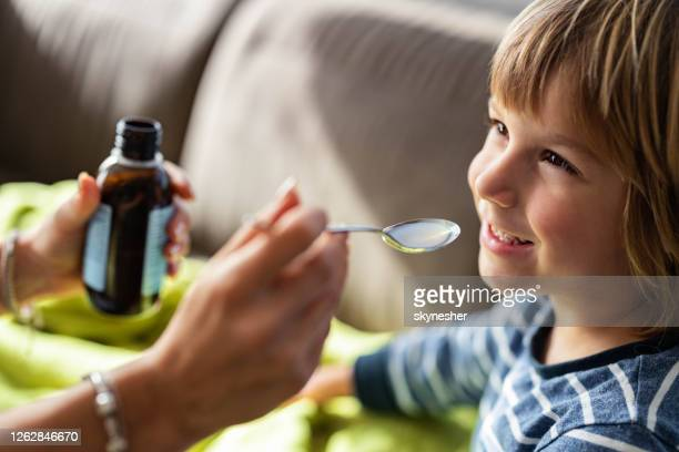 happy boy taking cough syrup from his parent at home. - syrup stock pictures, royalty-free photos & images