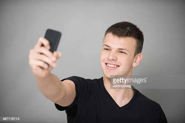 happy boy taking self portrait with smart phone - handsome black boy stock photos and pictures