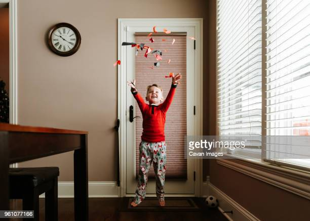 happy boy throwing confetti while standing on doormat by door at home - human doormat foto e immagini stock
