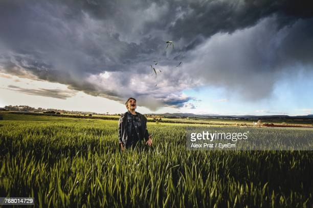 Happy Boy Throwing Grass While Standing At Farm Against Cloudy Sky