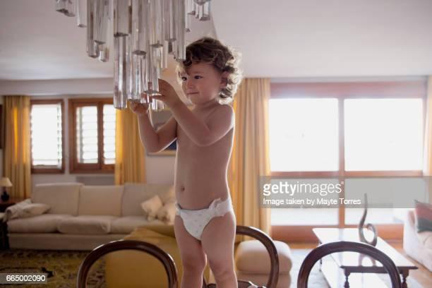 Happy boy touching a lamp