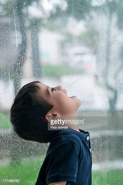 Happy boy watching the rain by the window