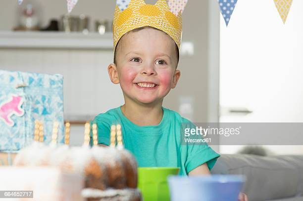 happy boy wearing paper crown sitting at birthday table - happybirthdaycrown stock pictures, royalty-free photos & images