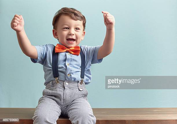 Happy boy wearing red bow tie, suspenders with hands in air