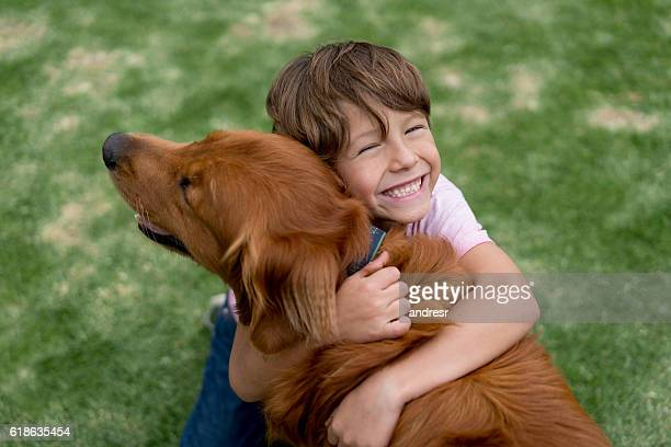 happy boy with a beautiful dog - abraçar - fotografias e filmes do acervo