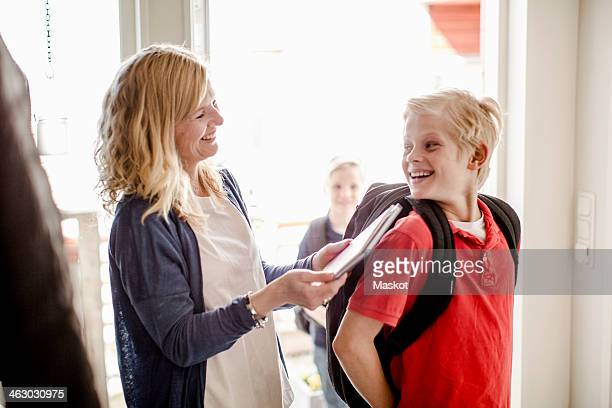 Happy boy with backpack looking at mother holding book