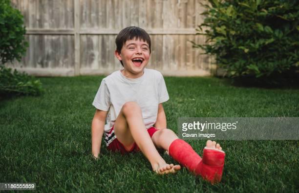 happy boy with broken leg sitting on grassy field in yard - gipsbein stock-fotos und bilder