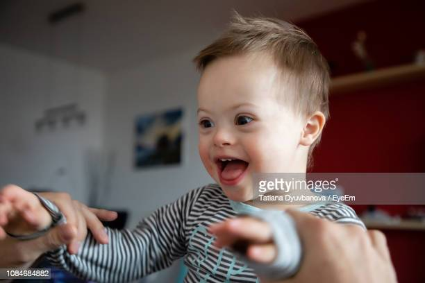 happy boy with down syndrome held by father at home - down syndrome stock pictures, royalty-free photos & images