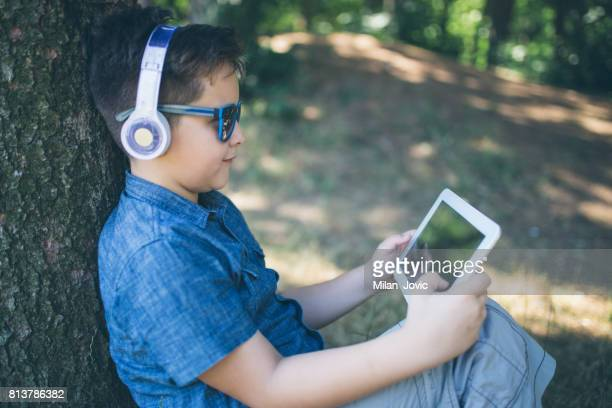 Happy boy with headphones listening to music in park