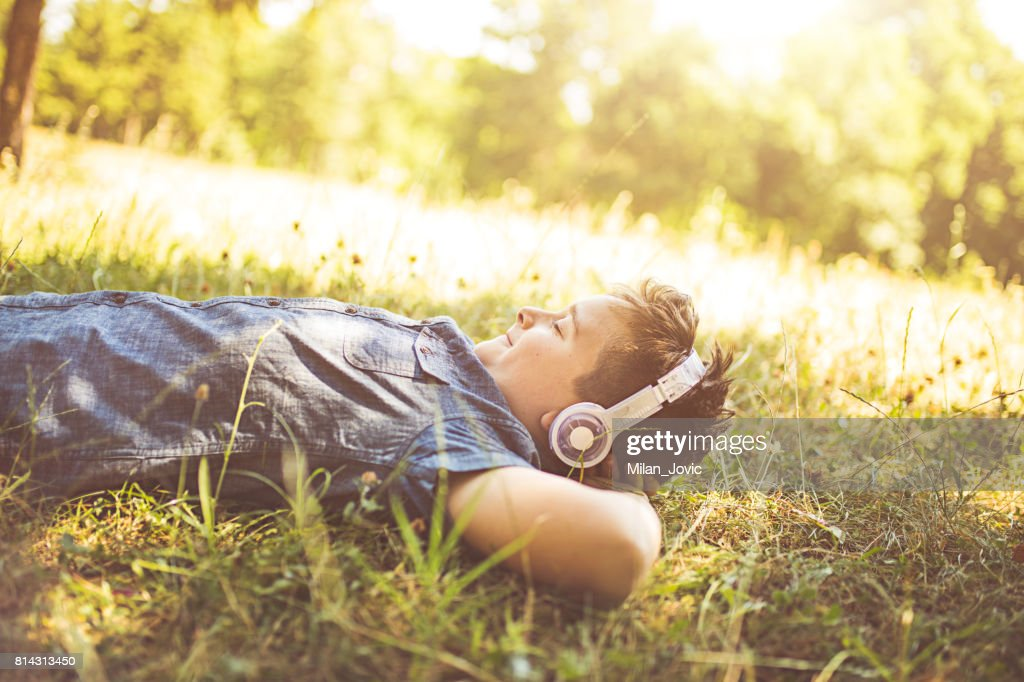 Happy boy with headphones listening to music in park : Stock Photo