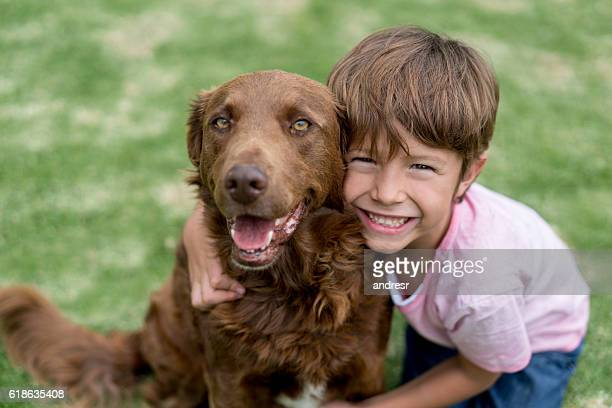 happy boy with his adopted dog - adoptie stockfoto's en -beelden