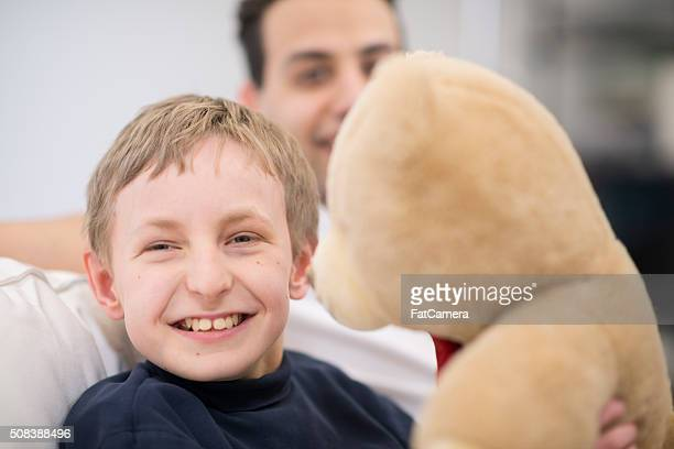 happy boy with his teddy bear - autism spectrum disorder stock photos and pictures