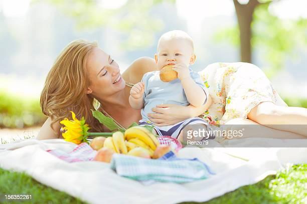 Glückliche junge mit Mutter Essen im park