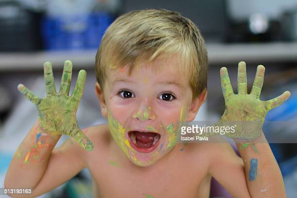 Happy boy with painted hands and face