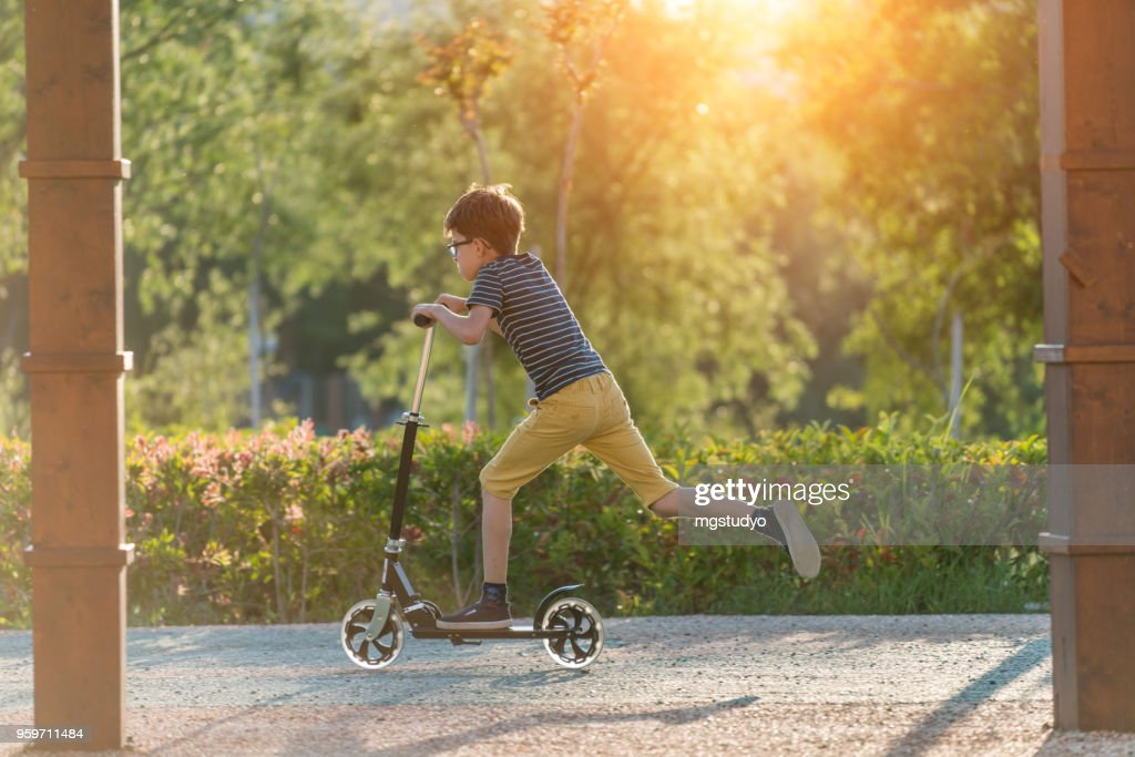 Happy Boy with scooter in a park : Stock Photo