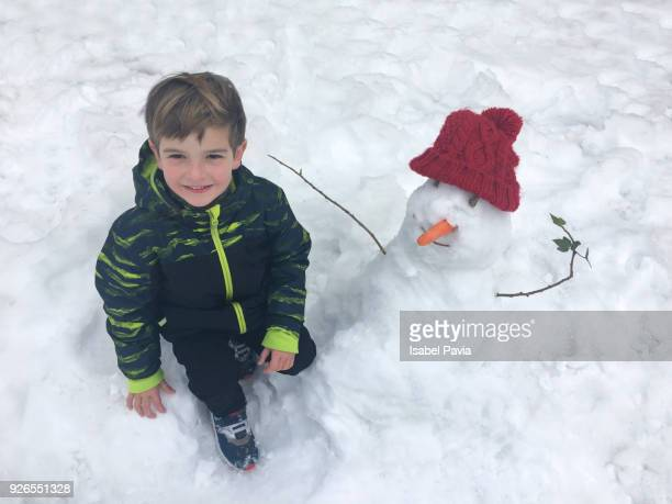 Happy boy with snowman in snowy park