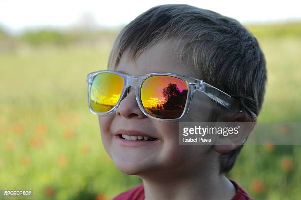 Happy boy with sunset reflection on sunglasses