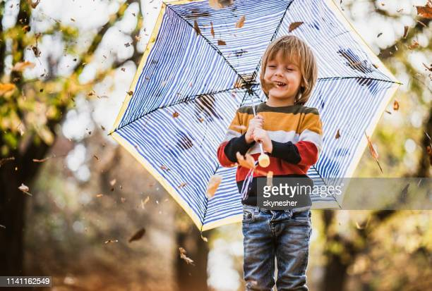 happy boy with umbrella in autumn day. - only boys stock pictures, royalty-free photos & images
