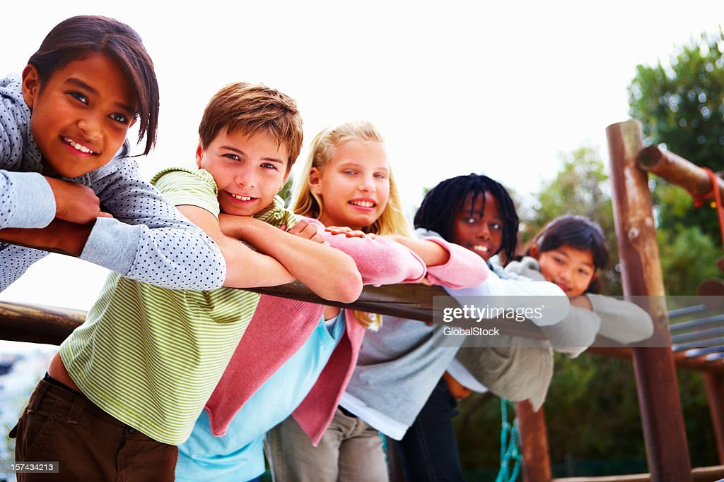 Happy boys and girls leaning on railing : Stock Photo
