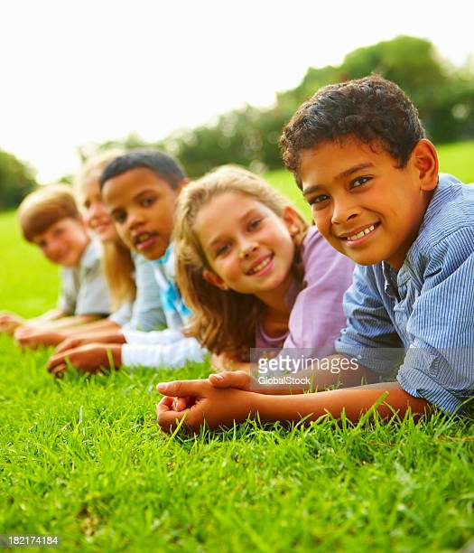 happy boys and girls lying in the grass at a park - lying on front stock pictures, royalty-free photos & images