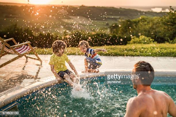 happy boys having fun while being splashed by their father from the swimming pool. - swimming pool stock pictures, royalty-free photos & images