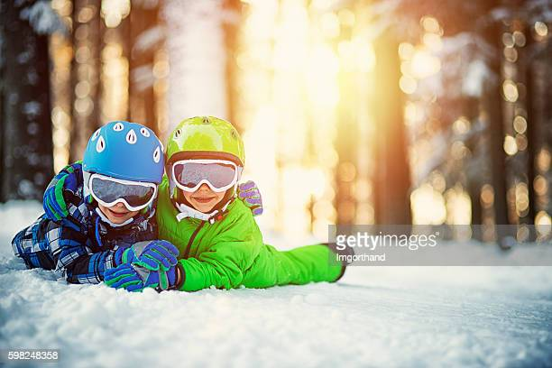 Happy boys in ski outfits enjoying winter