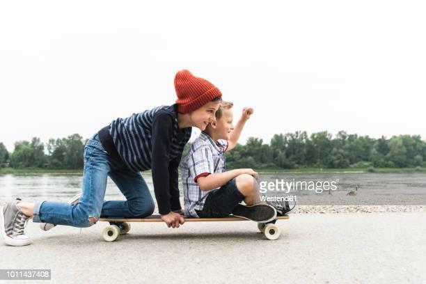 happy boys on skateboard at the riverside - 8 9 jahre stock-fotos und bilder